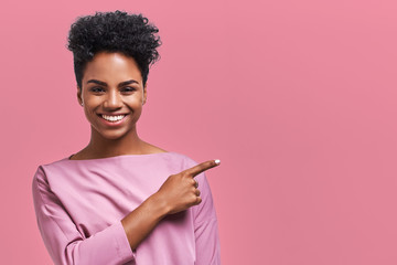 Horizontal portrait of happy dark skinned mixed race female model indicates with fore finger at blank copy space, shows place for your advertisement or promotional text. Lovely African American girl