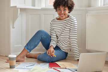 Happy African American student makes presentation for course paper, searches infromation on laptop computer, sits bare foot on floor, wears striped sweater and jeans, drinks hot latte or cappucino