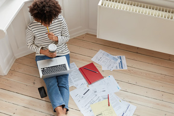 Top view of busy freelancer with Afro haircut, works on online project, holds takeaway coffee, focused into laptop computer, sits on wooden floor with many papers. Student involved in studying process