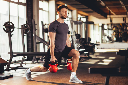 Handsome man legs workout with kettlebell in the gym