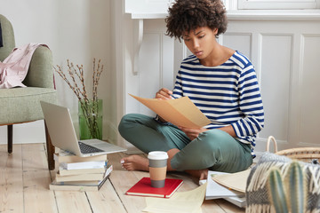 Photo of financial manager creats report in cozy place, sits crossed legs near opened laptop, holds papers, develops strategy for making business, uses books, drinks coffee, sits in modern apartment