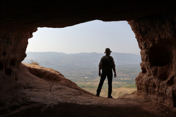 ISOLATED MAN WITH BACKPACK AND HAT AT THE ENTRANCE OF A CAVE