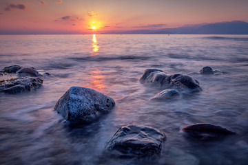 Long exposed photo of stones in the water of Mediterranean sea at sunrise. Crete, Greece