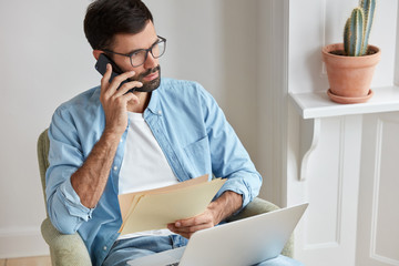 Photography of serious entrepreneur hears about achievement of his company, has telephone conversation with assistant, discuss details of business meeting, holds paper documents, sits in armchair