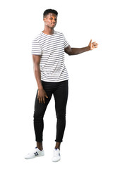 Full body of Dark skinned man with striped shirt pointing back with the index finger presenting a product on white background