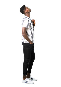 Full body of Dark skinned man with striped shirt stand and looking up on white background