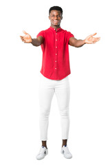 Full body of Young african american man presenting and inviting to come with hand. Happy that you came on white background