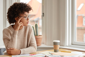 Photo of contemplative woman with Afro hairstyle, wears round spectacles, casual warm sweater, thinks about something while sits at desktop, drink coffee, poses near window indoor. Work concept