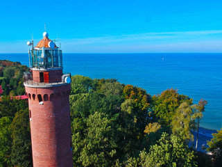 Foto auf AluDibond Leuchtturm Aerial view at red lighthouse, at baltic sea coast with forest and buildings.