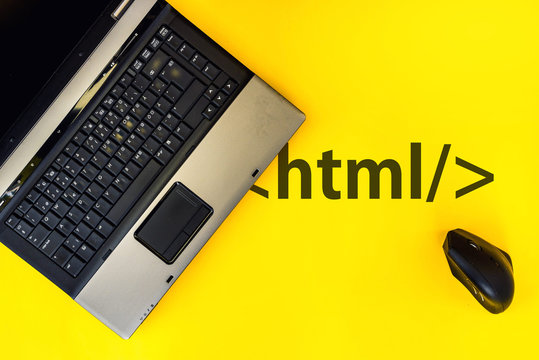 HTML Hyper Text Markup Language. laptop and vertical mouse on yellow background with html tag
