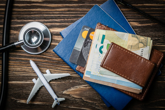 Medical tourism concept - passports, stethoscope, airplane, money top view