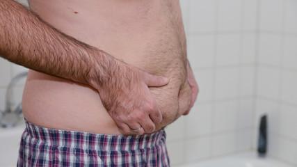 Übergewichtiger Mann steht im Bad und kontrolliert sein Bauchfett