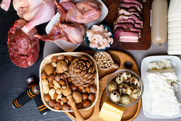 High protein food for body builders of lean steak, pork pate,milk, cheese, chicken, shrimps eggs beans,nuts, with dumbbell weights
