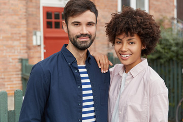 Two mixed race girl and boy stand closely to each other, being in good mood, have stroll outdoor, pose near rural building, have satisfied expressions at camera, enjoy sunny day. Relationships