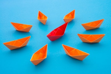 Leadership concept. Red paper boat origami motivate meeting with small orange boat on blue background. Leadership skills need for top management in organization, company ex. supervisor, manager, CEO