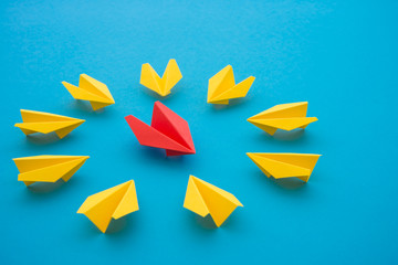 Leadership concept. Red paper plane origami motivate meeting with small yellow plane on blue background. Leadership skills need for top management in organization, company ex. supervisor, manager, CEO