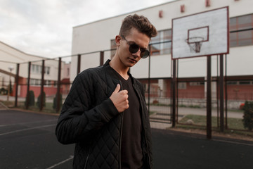 Handsome young guy with trendy sunglasses in stylish black clothes at the stadium outdoors