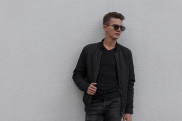 Fashionable young guy with sunglasses in a black jacket and a black t-shirt near the gray wall