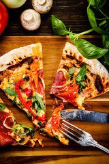 Pizza with pepper,salami and champignon on wooden table