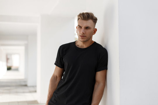 Handsome young american stylish man with hairstyle in fashion black shirt standing near white wall