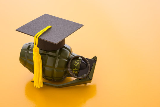 Graduation cap on hand bomb and yellow background. Education reform due to digital disruption or innovation technology concept. University degree is not important in future. No reform is dangerous.