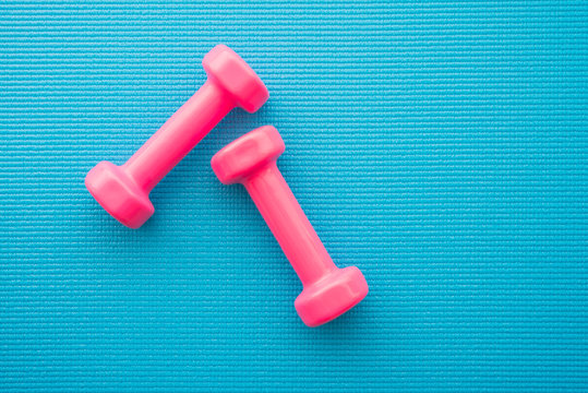 Flat lay of pink dumbbells for fitness exercise on blue yoga mat background in fitness center - Health care, diet and exercise concept