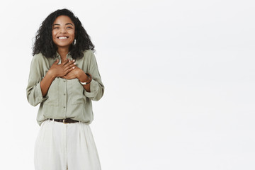 Charming charismatic and delighted cute african american young mom with curly hair in stylish outfit feeling grateful and happy receiving surprise gift from kid holding palms on heart, smiling
