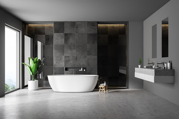 Black tile bathrom interior, tub and sink
