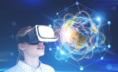 Fototapete - Woman in vr glasses looking at earth as atom