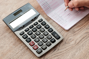 The fingers are holding the pencil. Below is a white screen calculator, a bank book,  placed on a wooden desk.