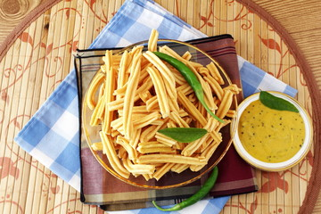 traditional indian gujrati tea time snack food ganthia or  fry noodles of chickpea flour or besan with chutny in wooden background