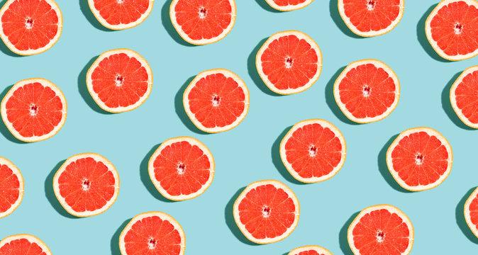 Halved fresh grapefruits on bright color background