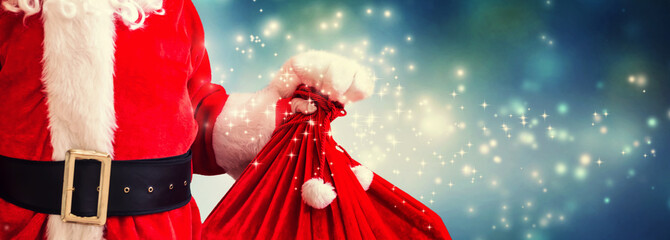 Santa holding a red sack in snowy night