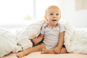 Cute 8 months baby girl on bed on the morning