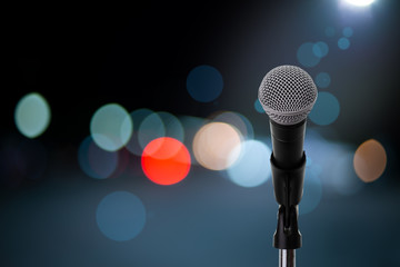 Microphone on stage ..Close up of microphone setting on stand with colorful light bokeh background in concert hall ,showbiz concept.