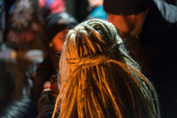 Girl with white dreadlocks at night, close-up