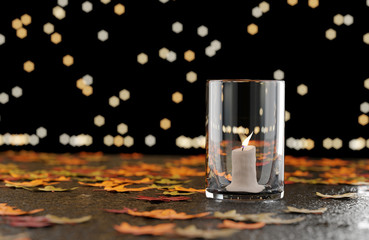 Glass Cup Of Light Candle with leaves on the floor, 3D rendering.