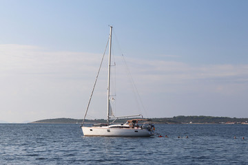 A modern sailing yacht is anchored in a bay. People bathe in the sea. Active rest on the Adriatic Sea of the Mediterranean region. Dalmatian riviera of Croatia. Prestigious and rich lifestyle