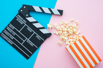 Cinema clapperboard and popcorn in paper bag on pink blue colorful background - Movie cinema entertainment concept