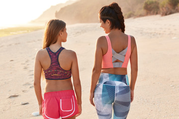 Back view of spoty women go in for sport together, walk across seashore, wears tops and shorts or leggings, discuss something, like active lifestyle, have outdoor training. Companionship concept