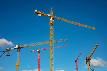 Yellow tower crane on blue sky background