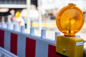 Construction safety. Street barricade with warning signal lamp on a road, blur site background