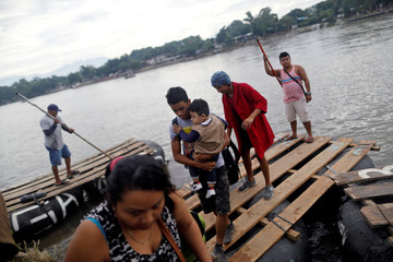 Honduran migrants, part of a caravan trying to reach the U.S., come down from a raft after crossing the Suchiate River on a raft to avoid the border checkpoint in Ciudad Hidalgo