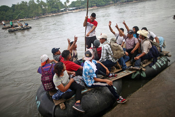 Honduran migrants, part of a caravan trying to reach the U.S., raise their hands as they cross the Suchiate River on a raft to avoid the border checkpoint in Ciudad Hidalgo