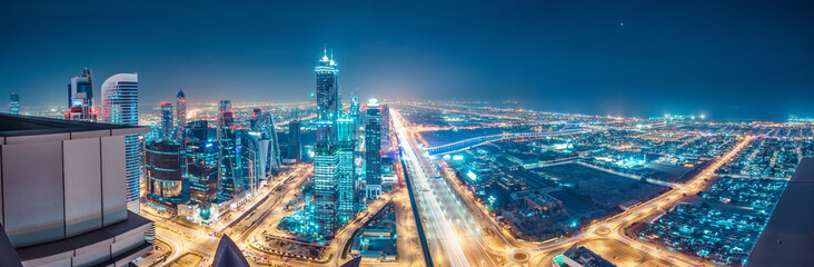 Spectacular urban skyline with colourful city illuminations. Aerial view on highways and skyscrapers of Dubai, United Arab Emirates. Fotobehang