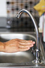 Hand open or close a water tab in kitchen.