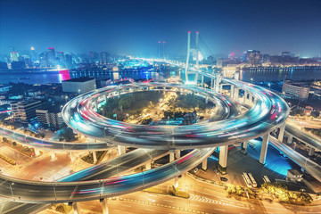 Scenic aerial view on famous bridge in Shanghai, China at night. Multicolored nighttime skyline. Travel background.