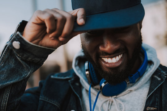Close up of a positive stylish afro american man smiling while wearing his trendy cap