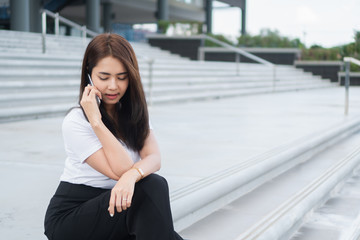 Young asian business woman in casual calling someone on phone and looking away.