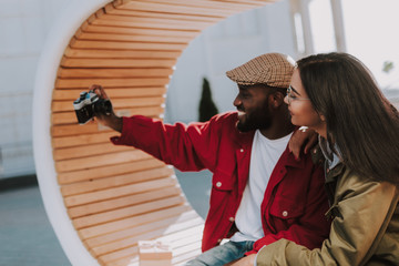 Cheerful happy afro American man using his camera while making photos with his loving girlfriend